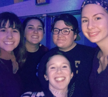 Five young women taking a selfie together at a roller skating rink.