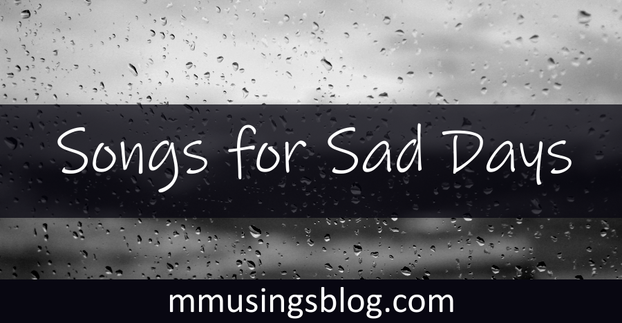 """Image with raindrops on a window and text """"Songs for Sad Days."""""""