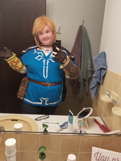 photo of a girl wearing a costume looking in bathroom mirror