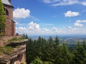 photo depicting a mountain overlook with trees, blue sky, and a town in the distance