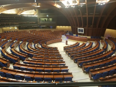 a large, round room with brown and blue chairs and desks arranged around a podium