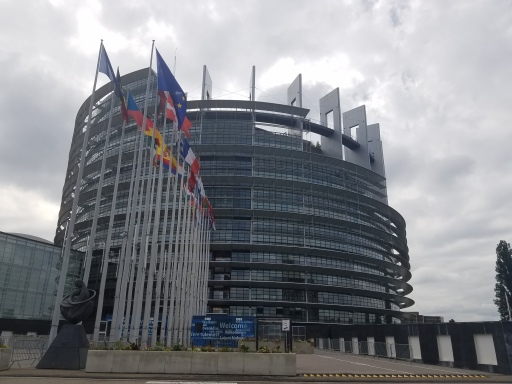 Photo of a large round building with rows of flags from European countries outside