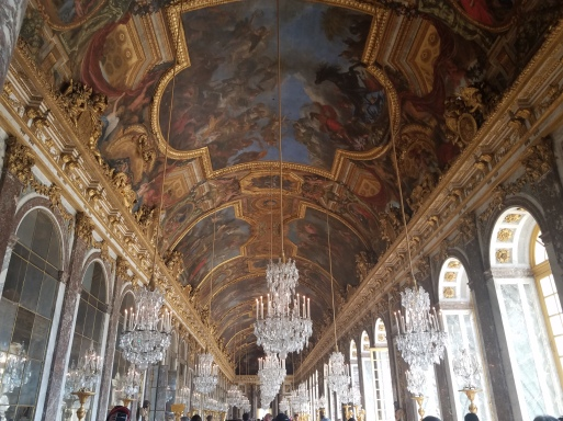 large hall in Versailles with paintings on the ceiling and many chandeleirs