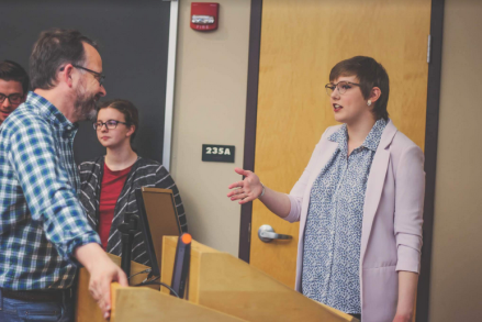 photo of young woman speaking with a professor in a classroom