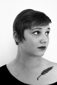 black and white photograph of a young woman with short hair and a feather pen tattoo on her collarbone. Sarah Henry.