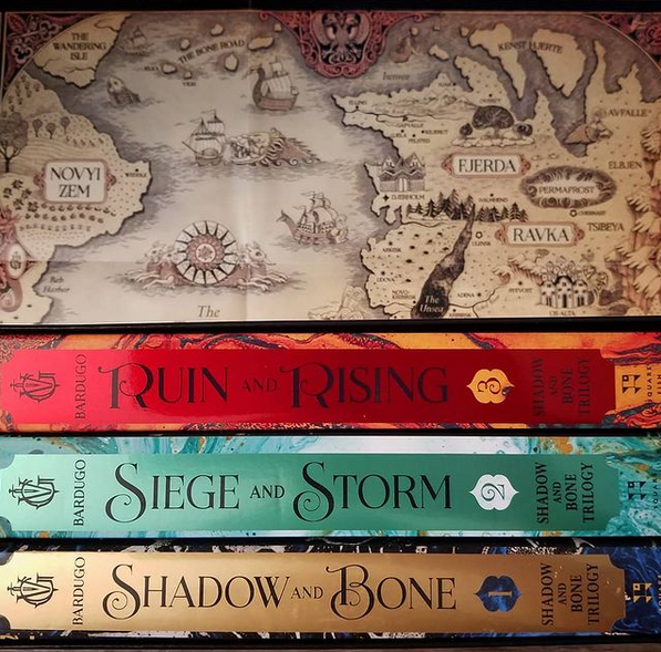 Photo of three books in front of a fictional map of Leigh Bardugo's Grishaverse. The books are, from top to bottom, Ruin and Rising, Siege and Storm, and Shadow and Bone.