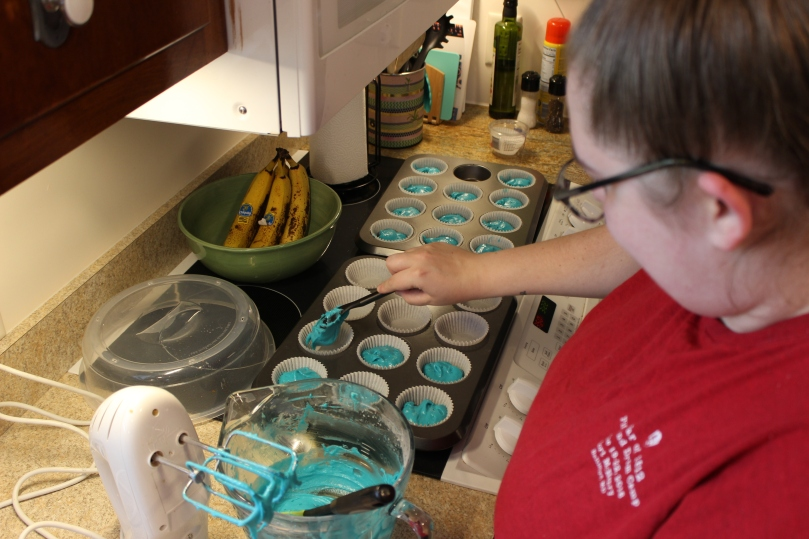 woman scooping blue cake batter out of a bowl and putting it into cupcake tins